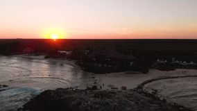 Aerial footage of a rock jetty beside a beach with a crowd of people gathered to watch the sunset. Aerial footage of a rock jetty beside a beach with a crowd of stock video footage