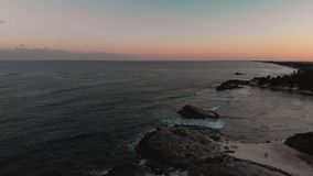 Aerial footage of a rock jetty beside a beach with a crowd of people gathered to watch the sunset. Aerial footage of a rock jetty beside a beach with a crowd of stock video