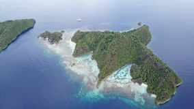 Aerial Footage of Scenic Islands in Raja Ampat. The scenic limestone islands in Wayag, Raja Ampat, are surrounded by healthy, shallow coral reefs. This remote stock footage