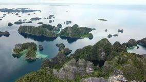 Aerial Footage of Scenic Islansd in Raja Ampat. The scenic limestone islands in Misool, Raja Ampat are surrounded by healthy, shallow coral reefs. This remote stock video footage
