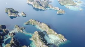 Aerial Footage of Scenic Rock Islands in Raja Ampat. The scenic limestone islands near Misool, Raja Ampat, are surrounded by healthy, shallow coral reefs. This stock video footage