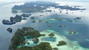 Aerial Footage of Scenic Tropical Islands in Raja Ampat. The scenic limestone islands in Misool, Raja Ampat are surrounded by healthy, shallow coral reefs. This stock footage