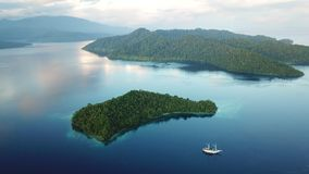 Aerial Footage of Scenic Tropical Islands in Raja Ampat. The scenic limestone islands near Batanta, Raja Ampat, are surrounded by healthy, shallow coral reefs stock footage