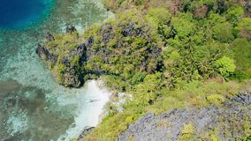 Aerial footage of small beach near big lagoon with lonely banca local boat on paradise sandy beach. Miniloc island El stock footage
