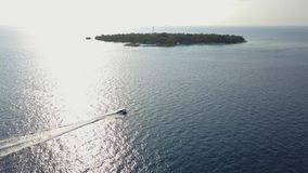 Aerial footage top view with motor boat at high speed cuts the waves while is leaving a long white trail. Conceptual. Aerial footage top view with motor boat at stock footage