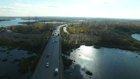 Aerial footage of traffic at bridge. Flying over Samara river. Car traffic at the  bridge.  Drone moving backwards. 4K Aerial stock footage shot at autumn season stock video footage