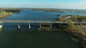 Aerial footage of traffic at bridge. Flying over Samara river. Car traffic at the  bridge.  Drone moving forward. 4K Aerial stock footage shot at autumn season stock video footage