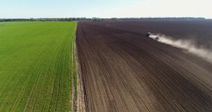 Aerial footage of a two tractors on a field. Tractor plows a field in the spring accompanied by plow. Tractor plowing a field and makes a lot of dust stock video