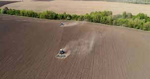 Aerial footage of a two tractors on a field. Tractor plows a field in the spring accompanied by plow. Tractor plowing a field and makes a lot of dust stock video footage