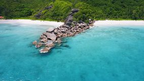 Aerial footage of unique granite huge boulders nature surge surrounded by crystal clear turquoise blue ocean water of. Grand and Petite Anse paradise like stock video footage