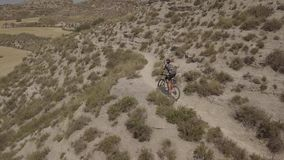 Aerial footage of a unrecognizable man riding fast a mountain bike along a path in a rural landscape. Aerial view of a biker riding a mountain bike on a rural stock video