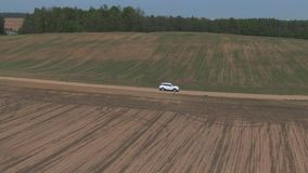 Aerial footage. White car rides on the field stock footage