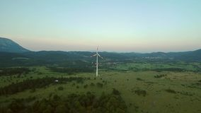 Aerial footageof a wind turbine at sunset - high angle view of a wide landscape.  stock video