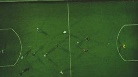 Aerial football match play. Clip. Aerial shot Two teams playing ball in football outdoors, top view. Football game. Outdoors, green field with markings, players stock footage
