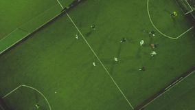 Aerial football match play. Clip. Aerial shot two teams playing ball in football outdoors, top view. Football game. Outdoors, green field with markings, players stock video