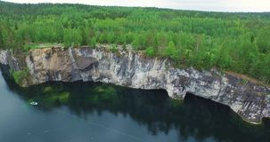 Aerial forest glade on cliff with tourists lake with boat stock footage