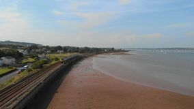 An aerial forward footage of a moving express train along the rising sea under a majestic blue sky and some white clouds stock video