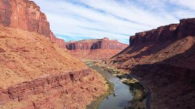 Aerial Forward Over Highway Passing By Colorado River In Canyon With Red Rocks