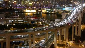 Time lapse,fast cars on overpass interchange,Brightly lit urban building. Aerial freeway busy city rush hour heavy traffic jam highway Shanghai at night,fast stock footage