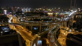 Slow moving cars on overpass interchange,Brightly lit urban building,shanghai. Aerial freeway busy city rush hour heavy traffic jam highway Shanghai at night stock video