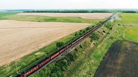 AERIAL: Freight train crossing railroad bridge. Rail freight transport delivering goods. 4K stock footage