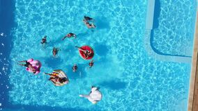 Aerial of friends having party in swimming pool with inflatable flamingo, swan, mattress. Happy young people wave hands