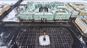 Aerial front view at the Winter Palace building, exterior with snow Palace Square and Aleksandr Column at winter season. Top view. Royalty Free Stock Images