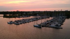 Aerial full HD footage video of yacht club marina at bay of lake Ontario. Shot with drone at sunset hour. Beautiful bright orange sky and sun reflection in the stock video