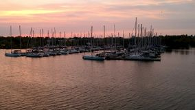 Aerial full HD footage video of yacht club marina at bay of lake Ontario. Shot with drone at sunset hour. Beautiful bright orange sky and sun reflection in the stock footage