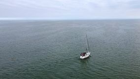 Aerial full HD video of yacht sailing in open water. Aerial full HD footage video of sail boat / yacht sailing in open water. Shot with drone at lake Ontario stock video footage