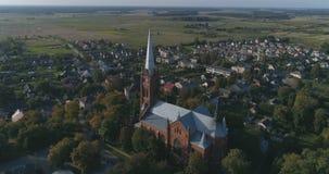 aerial Glatter Punkt des Interessenbrummens schoss von Kirche Johannes von Ramygala in Litauen Panorama der Stadt im Frühherbst 4 stock video footage