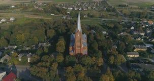 aerial Glatter Punkt des Interessenbrummens schoss von Kirche Johannes von Ramygala in Litauen Panorama der Stadt im Frühherbst 4 stock video