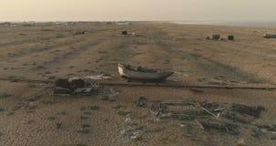 aerial Glatter Punkt des Interessenbrummenschusses um verlassenes Boot auf den Gebieten von Dungeness, in Vereinigtem Königreich  stock video