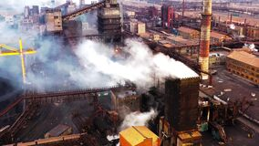 Aerial. GLOBAL WARMING. View of high chimney pipes with grey smoke. Pipes Pollute Industry Atmosphere With Smoke Ecology