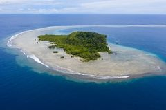 Aerial of Gorgeous Island and Reef in Papua New Guinea. A barrier reef surrounds a gorgeous, tropical island in Papua New Guinea. This remote, tropical area is royalty free stock image