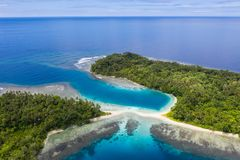 Aerial of Gorgeous Islands and Reef in Papua New Guinea. Reefs surround gorgeous, tropical islands in Papua New Guinea. This remote, tropical area is part of the stock photos