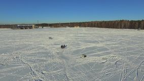 Aerial, group fishermen on the frozen lake in winter stock video