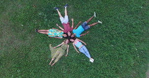 Aerial of group of friends forming a star shape lying in grass stock footage