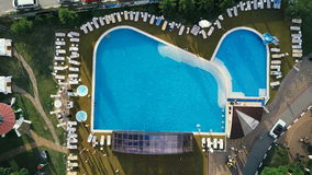 Aerial helicopter shot of a pool with swimmers. Zooming in and out. Aerial helicopter shot of a pool with swimmers. Flying down and zoom in stock footage