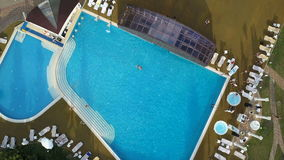 Aerial helicopter shot of a pool with swimmers. Zooming in and out. Aerial helicopter shot of a pool with swimmers. Flying up and zoom out stock footage