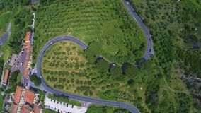 Aerial helicopter view of grassy valley, village and winding road in Italy. Stock footage stock footage
