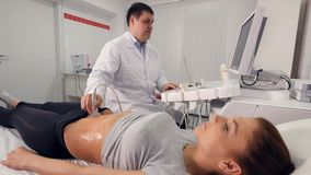 Aerial high angle of the process of ultrasound examination of the abdominal cavity. Aerial high angle of the doctor making the ultrasound examination of the stock footage
