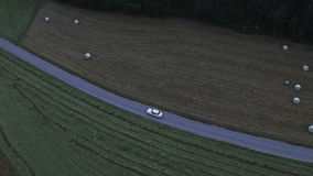 Aerial: high angle view of a white car driving on asphalt road between fields stock video footage