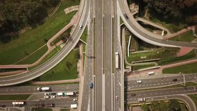 Aerial high drone flight over evening road traffic. Highway and overpass with cars and trucks, interchange, two-level road junctio. N. Top view.. City stock footage