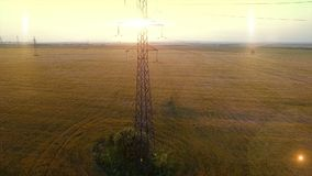 AERIAL High-voltage tower summer warm evening light camera fly up near metal structure contour opposite sun natural stock footage