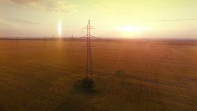AERIAL High-voltage tower summer warm evening light camera fly near electricity cable and metal structure