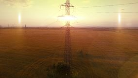 AERIAL High-voltage tower summer warm evening light camera fly up near metal structure contour opposite sun stock footage