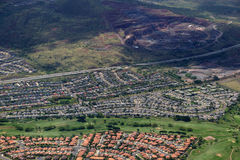 Aerial of Highway, Kapolei homes, golf course, and quarry on Oa stock photo