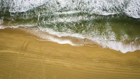 Green ocean on yellow sand stock photography