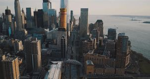 Aerial, huge skyscrapers and a wide street with traffic cars, on the background of the island of freedom. Aerial footage, huge skyscrapers and a wide street with stock video footage